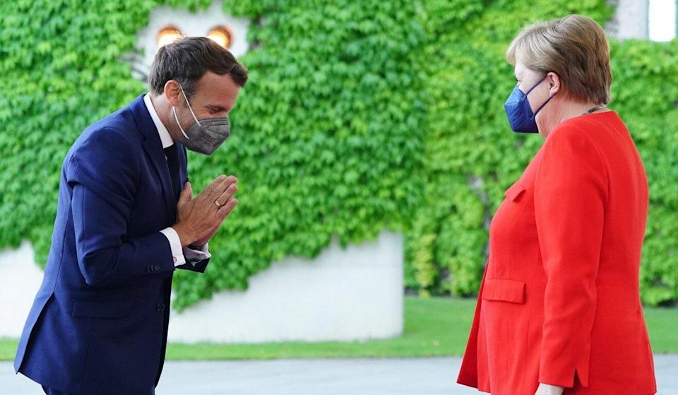 French President Emmanuel Macron bows in front of German Chancellor Angela Merkel as he arrives for their meeting at the Chancellery in Berlin on June 18. Photo: EPA-EFE