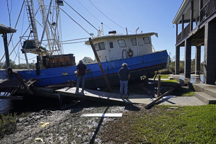 Boat owner Ricky Mitchell, left, and his friend Buck, no last name given, surveys damage to his boat that washed up against the home of Ray Garcia, in Lakeshore, Miss., Thursday, Oct. 29, 2020. Hurricane Zeta passed through Wednesday with a tidal surge that caused the boat to become unmoored. (AP Photo/Gerald Herbert)