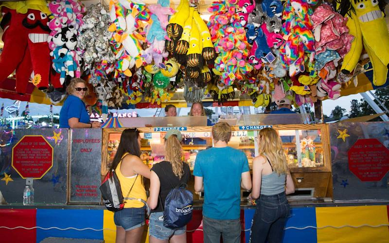 In addition to rides, fairgoers stay busy with a wide range of games and challenges. It's not uncommon to see people carrying overstuffed teddy bears or other trophies from their wins. | Jason Bergman