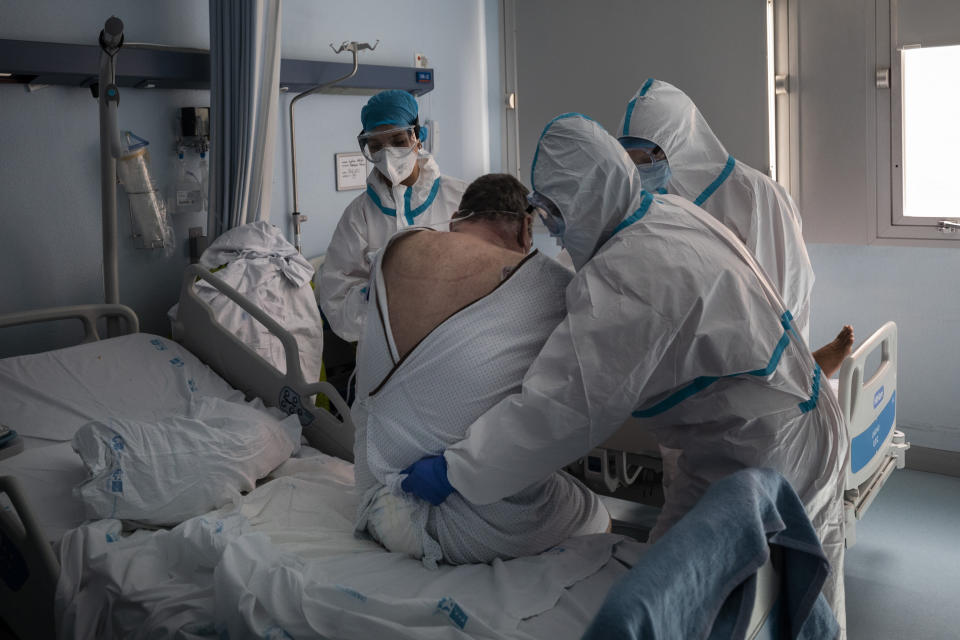 Patient Laurentiu Vania Hancu is lifted by a medical team during a physiotherapy session at the COVID-19 ward in the Severo Ochoa Hospital in Leganes on the outskirts of Madrid, Spain, Wednesday, Feb. 17, 2021. (AP Photo/Bernat Armangue)