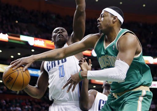 Boston Celtics' Paul Pierce, right, passes the ball under pressure from Charlotte Bobcats' Bismack Biyombo (0) in the first quarter of an NBA basketball game in Boston, Saturday, March 16, 2013. (AP Photo/Michael Dwyer)