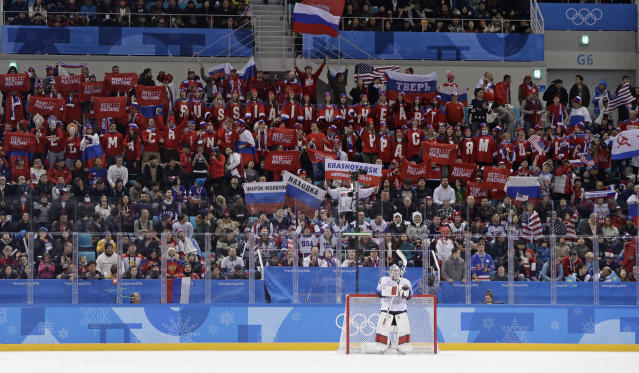 Supporters of Russian athletes cheer behind U.S. goalie Ryan Zapolski. (AP Photo/Matt Slocum)