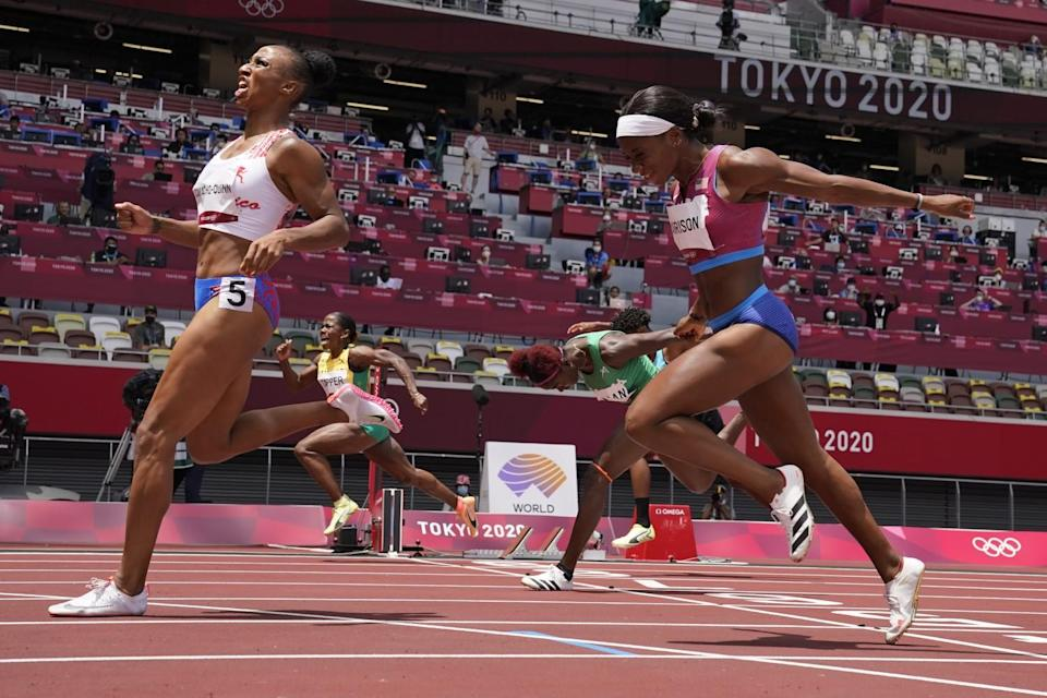 Female runners push past the finish line on the track.