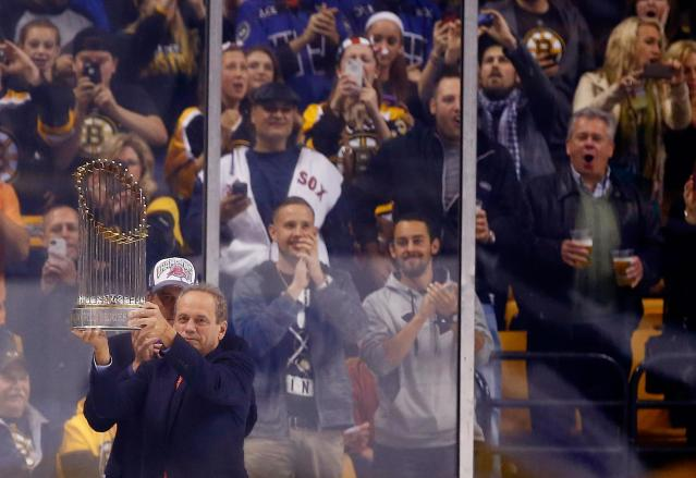 BOSTON, MA - OCTOBER 31: President and Chief Exective Officer Larry Lucchino of the Boston Red Sox raises the World Series trophy at TD Garden during the game between the Boston Bruins and the Anaheim Ducks on October 31, 2013 in Boston, Massachusetts. (Photo by Jared Wickerham/Getty Images)