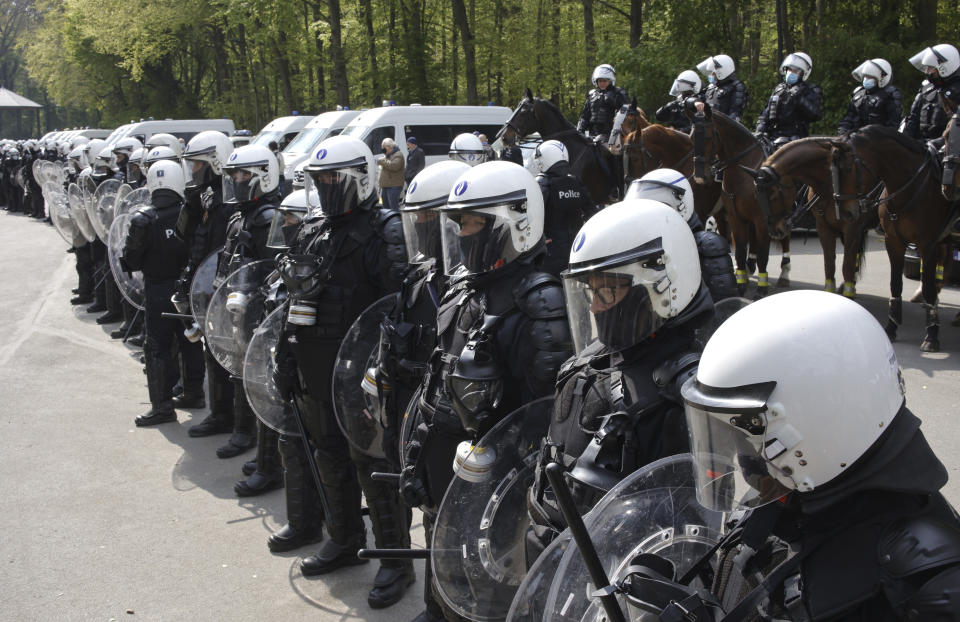 "Police in riot gear and on horseback form a line at the Bois de la Cambre park during a gathering called ""La Boum 2"" in Brussels, Saturday, May 1, 2021. Police put on extra patrols Saturday to monitor the gathering which is being held in defiance of Belgium's current COVID-19 regulations. (AP Photo/Olivier Matthys)"