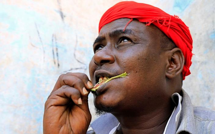 On the same day in Somalia'a capital, Mogadishu, a man enjoys chewing the leaf stimulant khat at his home.