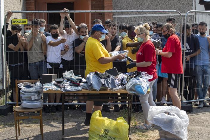 Lithuanians sell things to migrants standing behind the fence at the refugee camp in the village of Verebiejai, Lithuania, Sunday, July 11, 2021. European Union member Lithuania has declared a state of emergency due to an influx of migrants from neighboring Belarus in the last few days. Lithuania's interior minister said late Friday that the decision, proposed by the State Border Guard Service, was necessary not because of increased threats to the country of 2.8 million but to put a more robust system in place to handle migrants. (AP Photo/Mindaugas Kulbis)