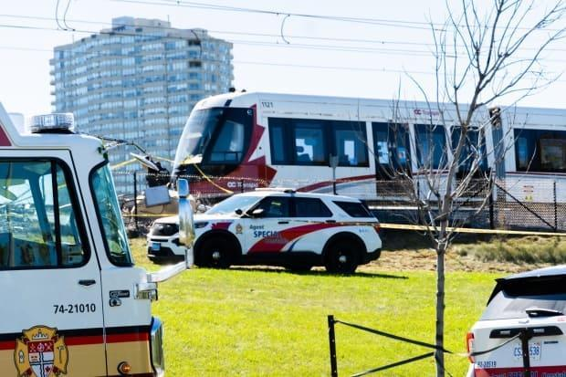 Emergency vehicles are parked near the scene of a derailed LRT train in Ottawa on Sunday. (Nicholas Cleroux/Radio-Canada - image credit)