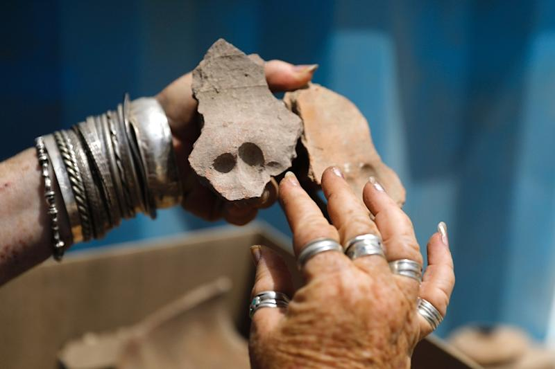 An Israel Antiquities Authority archaeologist shows shows pottery shreds with finger prints on them from the Byzantine time found during a large excavation in the central Israeli town of Gedera (AFP Photo/MENAHEM KAHANA)