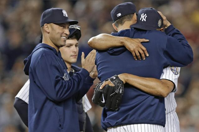 New York Yankees' Derek Jeter, left, applauds as retiring Yankees pitcher Andy Pettitte, back to camera, embraces relief pitcher Mariano Rivera in the ninth inning of Rivera's final appearance at a baseball game at Yankee Stadium, Thursday, Sept. 26, 2013, in New York. The Rays won 4-0. (AP Photo/Kathy Willens)