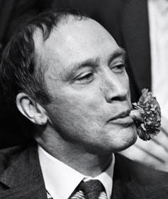 Pierre Trudeau with a carnation in his mouth.