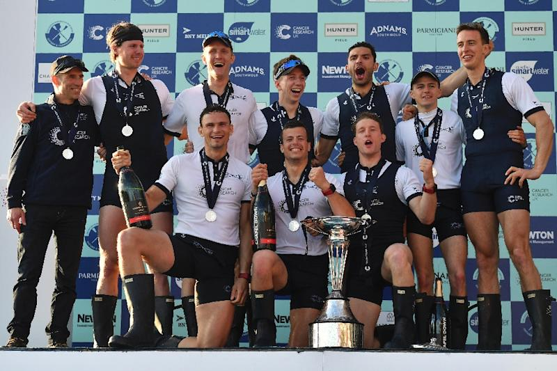 Oxford's Michael Disanto (C) poses behind the trophy with his crew members cox Sam Collier, Vassilis Ragoussis, James Cook, Michael Disanto, Oliver Siegelaar, Joshua Bugajski, Oliver Cook, Matthew O'Leary and William Warr on April 2, 2017 (AFP Photo/Ben STANSALL)