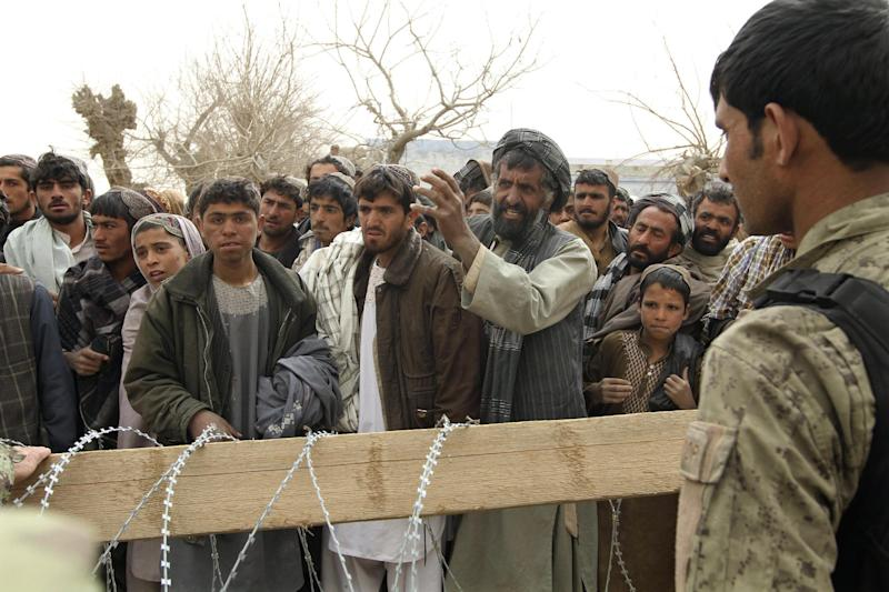 """An Afghan soldier speaks to civilians gathered outside a military base in Panjwai, Kandahar province south of Kabul, Afghanistan, Sunday, March 11, 2012. Afghan President Hamid Karzai says a U.S. service member has killed more than a dozen people in a shooting including nine children and three women. Karzai called the attack Sunday """"an assassination"""" and demanded an explanation from the United States. He says several people were also wounded in the attack on two villages near a U.S. base in the southern province of Kandahar. (AP Photo/Allauddin Khan)"""