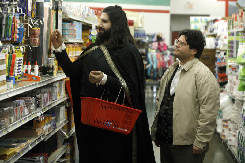 """This image released by FX shows Kayvan Novak and Harvey Guillen, right, in a scene from """"What We Do In the Shadows."""" The series premiering Wednesday is based on the 2014 cult-hit movie from New Zealand. (John P Johnson/FX via AP)"""