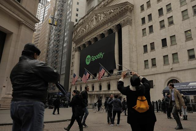 Pedestrians walk past a banner with the Spotify logo on it as the company lists its stock on the New York Stock Exchange with a direct listing in New York, U.S., April 3, 2018. REUTERS/Lucas Jackson