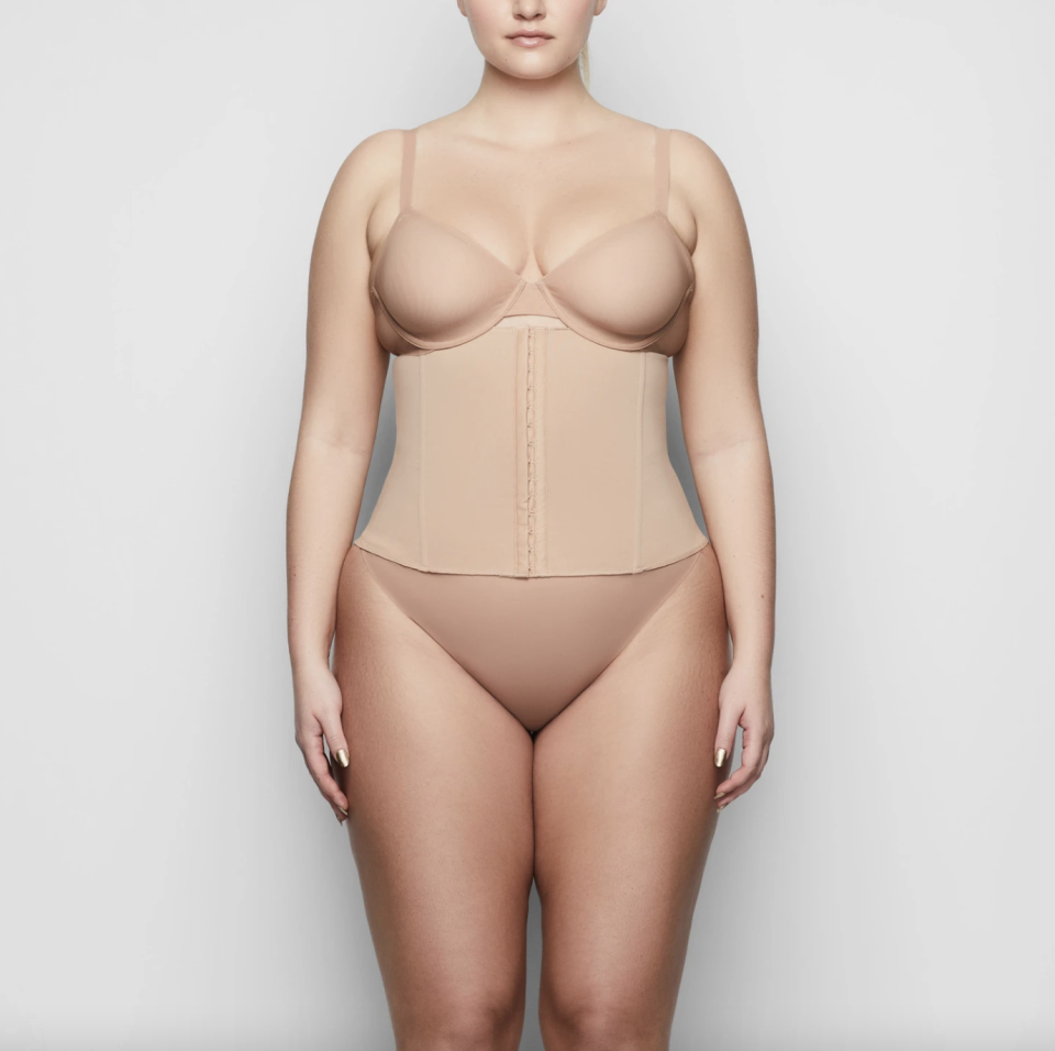plus size model wearing a nude coloured waist trainer from skims