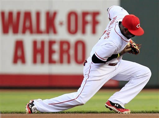 Cincinnati Reds second baseman Brandon Phillips fields a ground ball hit by Philadelphia Phillies' Chase Utley in the first inning of a baseball game, Tuesday, Sept. 4, 2012, in Cincinnati. Phillips threw Utley out at first. (AP Photo/Al Behrman)
