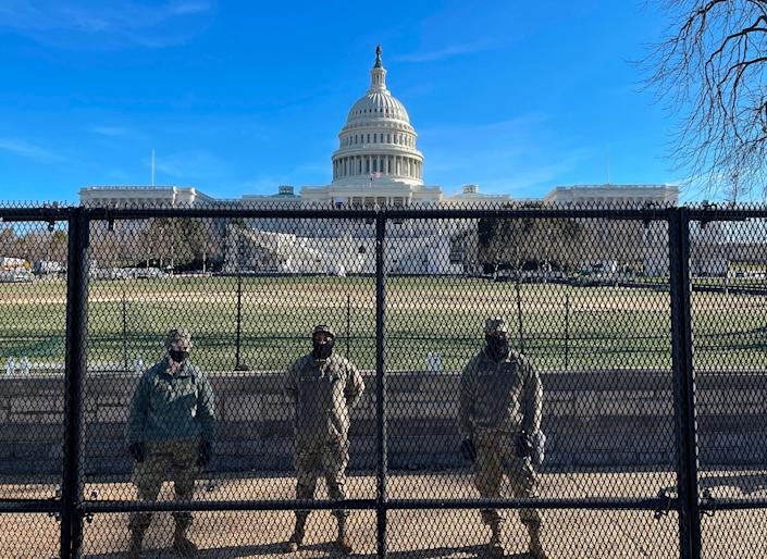 <p>National Guard soldiers guard the grounds of the US Capitol from behind a security fence in Washington, DC</p> (AFP via Getty Images)