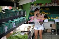 """Rosana Vieira Alves, 28, holds her two-year-old, daughter Luana Vieira, who was born with microcephaly, at a supermarket in Olinda, Brazil, August 9, 2018. Rosana has three daughters. """"It's hard to manage the girls. Some of them are jealous, but Luana needs more care. In time, they'll understand."""" Rosana does not have any family support and is overwhelmed by the cost of housing and Luana's medicines. She counts it a victory that she has managed to get a wheelchair for Luana, and worries about the four surgeries her daughter needs to correct problems with her eyes, her gut and the position of her hips and feet. The demands have taken Rosana to some dark places, and she confesses that she has considered suicide. But she still dreams of a better future, and hopes to get a degree in accounting or civil engineering. REUTERS/Ueslei Marcelino SEARCH """"ZIKA"""" FOR THIS STORY. SEARCH """"WIDER IMAGE"""" FOR ALL STORIES."""
