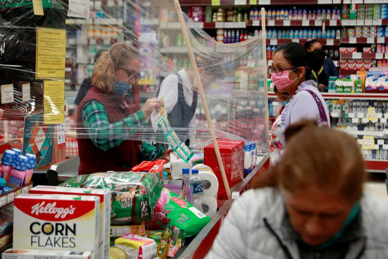FILE PHOTO: A cashier serves customer behind a makeshift plastic barrier as a preventive measure against the spread of the coronavirus disease (COVID-19) at Garis supermarket in Toluca