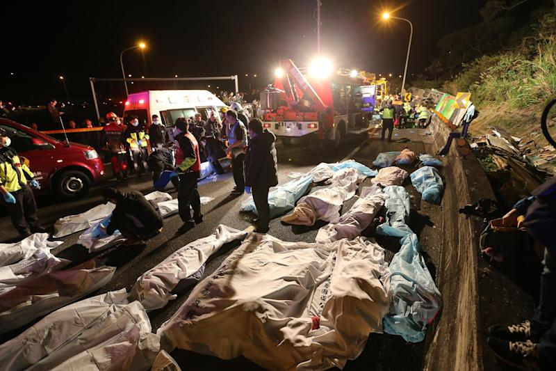 Bodies are covered at the scene of a crash where a bus collided with a car on a highway in Taipei, Taiwan, Monday, Feb. 13, 2017. A tour bus has flipped over on a highway near Taiwan's capital, killing over 30 people and trapping many others, officials said. (AP Photo)