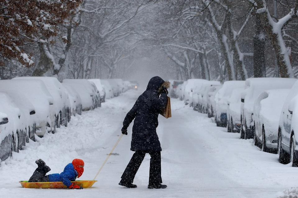 A woman pulls her child on a sled in heavy snow in Brooklyn, New York City, U.S. February 9, 2017. REUTERS/Brendan McDermid     TPX IMAGES OF THE DAY