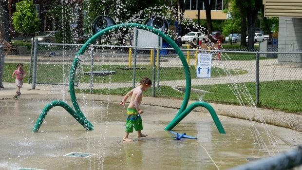A child walks over a splash pad in Winnipeg — one way to stay cool in the heat. (Jaison Empson/CBC - image credit)