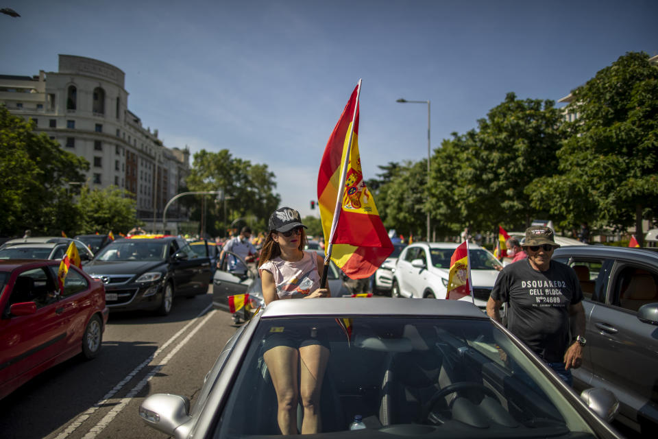 A woman waves a Spanish flag during a drive-in protest organised by Spain's far-right Vox party against the Spanish government's handling of the nation's coronavirus outbreak in Madrid, Spain Saturday, May 23, 2020. (AP Photo/Manu Fernandez)