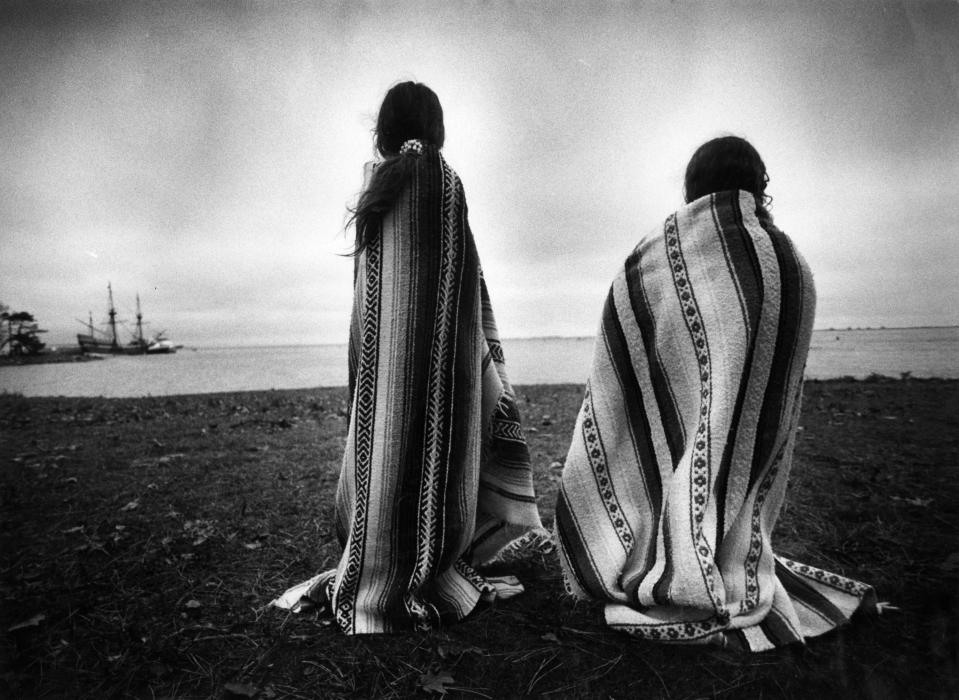 Sisters Weetoomoo Carey, 8, left, and Jackolynn Carey, 5, Wampanoag Nipmucs from Mashpee, looked across to the Mayflower replica anchored near Plymouth Rock in Plymouth, Mass. on Nov. 26, 1991. They were with a group of Native Americans gathered for a day of mourning in counterpoint to the Pilgrims' Thanksgiving. (Photo: Suzanne Kreiter/The Boston Globe via Getty Images)