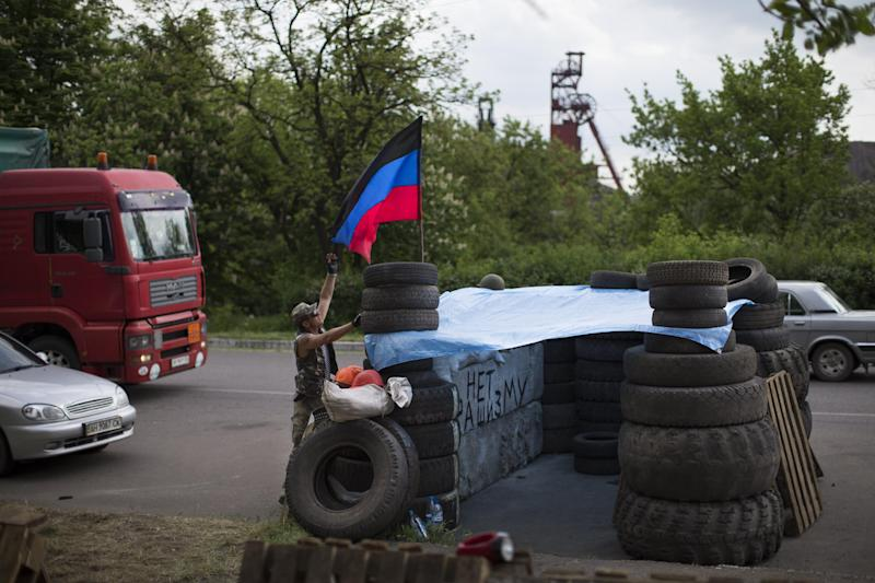 "Pro-Russian insurgents with the self-proclaimed Donetsk People's Republic man a checkpoint by the Karl Marx coal mine seen in the background near Korsun, a small town about 30 km north-east from Donetsk, eastern Ukraine, Tuesday, May 13, 2014. The words on the wall of barricades read "" No fascism"". The Donetsk People's Republic has proclaimed independence from Ukraine after a contentious autonomy referendum Sunday that has been rejected by the government and the international community. (AP Photo/Alexander Zemlianichenko)"