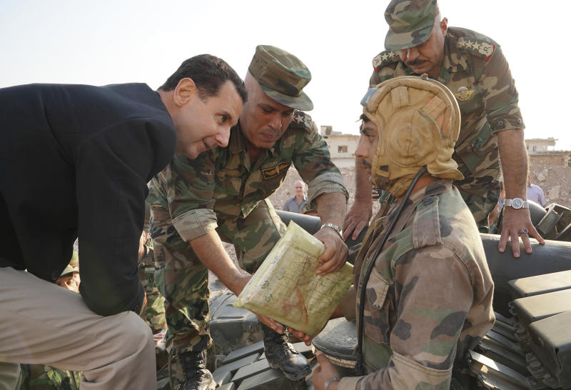 "In this photo released on the official Facebook page of the Syrian Presidency, Syrian President Bashar Assad, left, speaks with Syrian troops during his visit to the strategic town of Habeet, in the northwestern province of Idlib, Syria, Tuesday, Oct. 22, 2019. On Tuesday, Assad called the Turkish President Recep Tayyip Erdogan a ""thief"" during his first visit to territory captured from Turkey-backed rebels in the northwestern province of Idlib. (Facebook page of the Syrian Presidency via AP)"