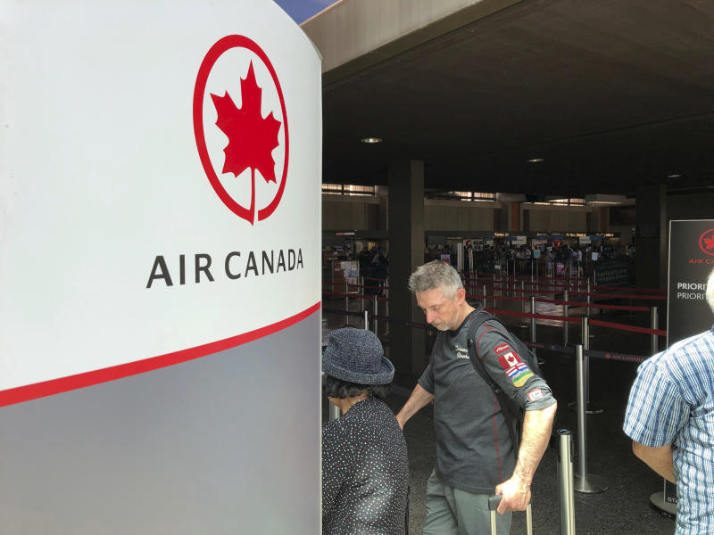 "Passengers from an Australia-bound Air Canada flight diverted to Honolulu Thursday, July 11, 2019, after about 35 people were injured during turbulence, stand in line at the Air Canada counter at Daniel K. Inouye International Airport to rebook flights. Air Canada said the flight from Vancouver to Sydney encountered ""un-forecasted and sudden turbulence,"" about two hours past Hawaii when the plane diverted to Honolulu. (AP Photo/Caleb Jones)"