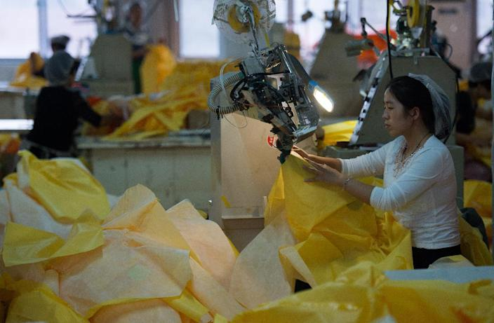 Factory workers make protective suit for use in handling people infected with Ebola, at Lakeland Industries Inc. in China on October 23, 2014 (AFP Photo/Johannes Eisele)