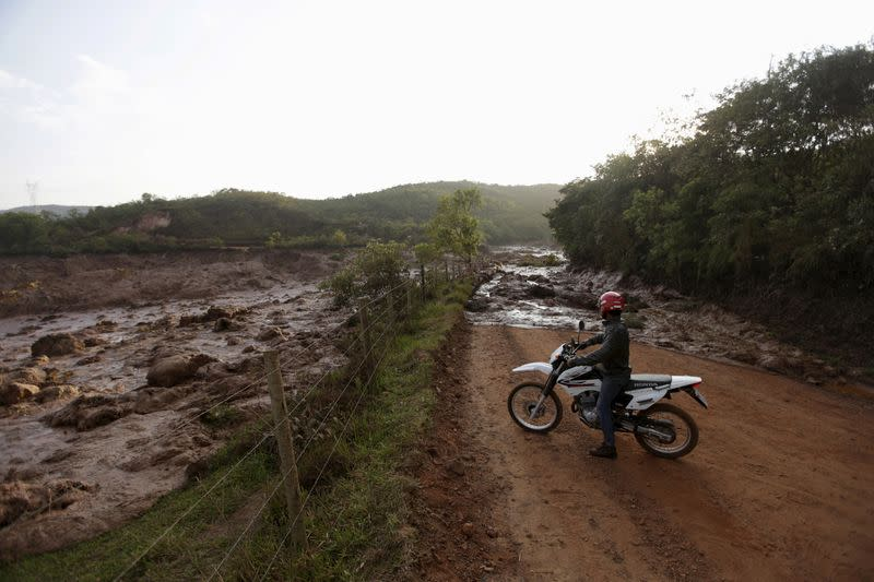 FILE PHOTO: A man observes a road blocked with mud after a dam owned by Vale SA and BHP Billiton Ltd burst in Mariana