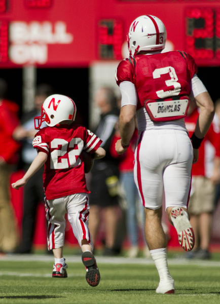 "FILE - In this April 6, 2013 file photo, Nebraska's Taylor Martinez (3) guides Jack Hoffman, then 6, of Atkinson, Neb., down the field for his touchdown play during a special segment dedicated to Hoffman during the second half of the Red-White spring NCAA college footballame at Memorial Stadium. The Upper Deck Co. issued a card for Jack, with signed blow-ups for his foundation to auction off. The winning bidder for the first card declined to pay. Jack's father, Andy Hoffman, says news coverage prompted three buyers to offer $10,000 each for a signed card. Among those stepping up: actor James Denton, who was on ""Desperate Housewives."" (AP Photo/Lincoln Journal Star, Matt Ryerson, File) LOCAL TV OUT; KOLN-TV OUT; KGIN-TV OUT; KLKN-TV OUT"