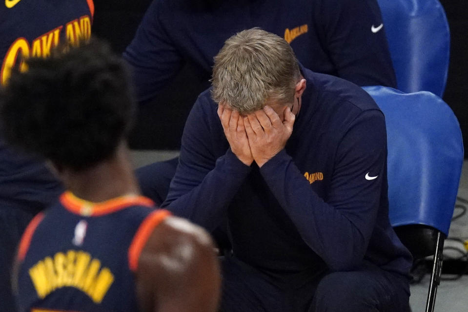 Golden State Warriors head coach Steve Kerr, right, puts his head in his hands after his team was charged with an offensive foul during the first half of an NBA basketball game against the Los Angeles Lakers Sunday, Feb. 28, 2021, in Los Angeles. (AP Photo/Mark J. Terrill)