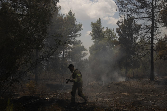An Israeli firefighter works to extinguish a fire, on the second day of wildfires near Jerusalem, Monday, Aug. 16, 2021. Israel Fire and Rescue service said in a statement on Monday, that 45 firefighting teams accompanied by eight planes were working to contain five fires in the forested hills west of the city. (AP Photo/Maya Alleruzzo)