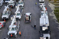 Workers gas up rows of trucks after a day's work at a tent city in Amelia, La., Thursday, Sept. 16, 2021. When Ida came ashore on Aug. 29, it knocked out power to about 1.1 million customers in the state. (AP Photo/Gerald Herbert)