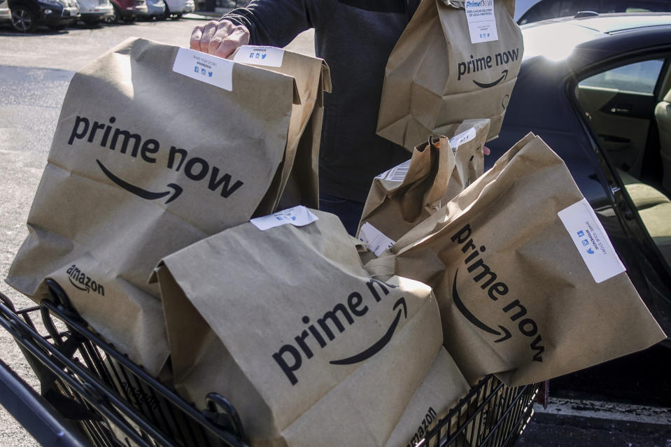 FILE - In this Feb. 8, 2018, file photo, Amazon Prime Now bags full of groceries are loaded for delivery by a part-time worker outside a Whole Foods store in Cincinnati. Amazon's Prime Day deals are coming to the aisles of Whole Foods, as the online retailer seeks to lure more people to its Prime membership after recently hiking up the price. (AP Photo/John Minchillo, File)