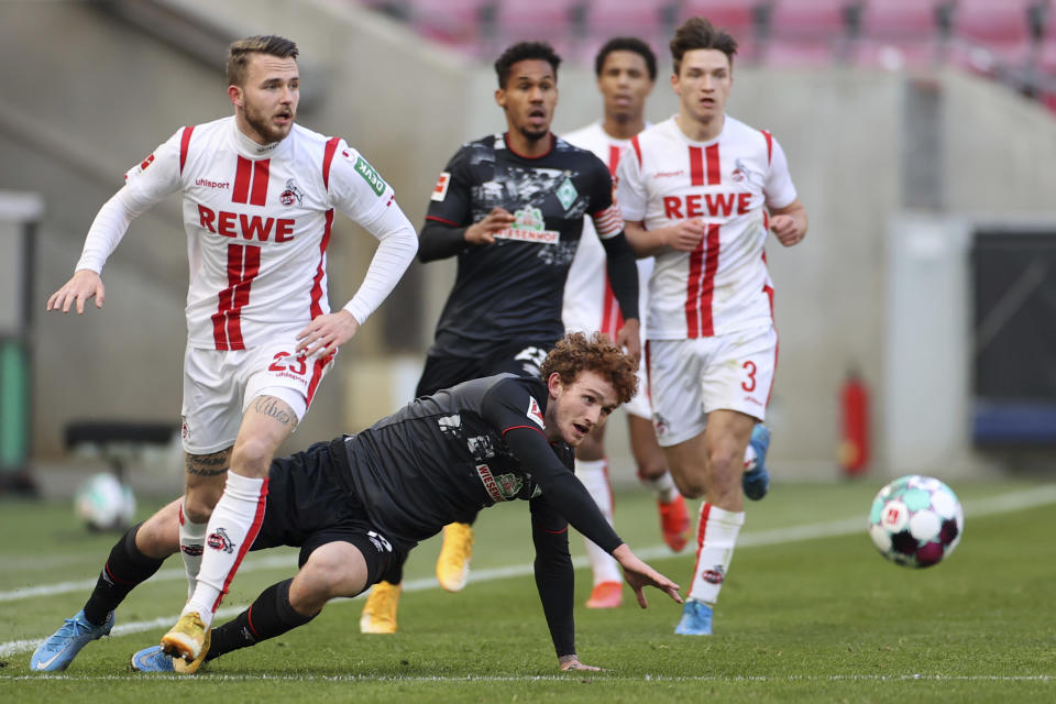 Cologne's Jannes Horn, left, and Bremen's Joshua Sargent, front right, challenge for the ball during the German Bundesliga soccer match between 1. FC Cologne and Werder Bremen in Cologne, Germany, Sunday, March 7, 2021. (Rolf Vennenbernd/dpa via AP)