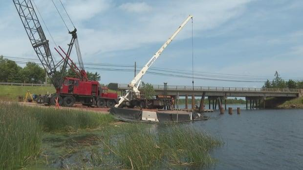 Crews are pounding heavy steel into place to support a temporary bridge that spans the river.  (Brian Higgins/CBC - image credit)