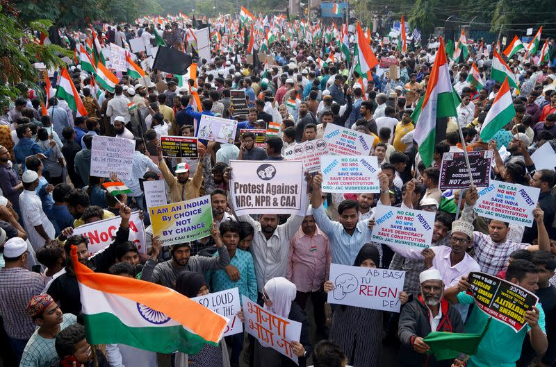 Demonstrators hold placards and flags as they attend a protest rally against a new citizenship law, in Hyderabad