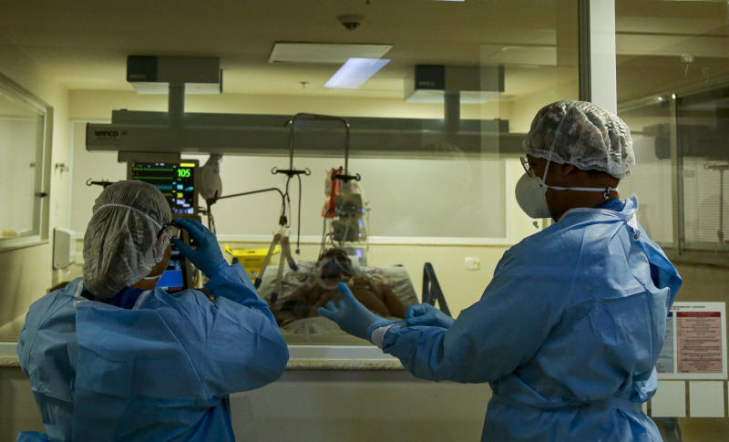 Health workers wearing protective suits get ready to enter an intensive care unit, where COVID-19 patients are treated, at the Emilio Ribas hospital in Sao Paulo, Brazil on April 20, 2020. - Brazil reported 40,581 confirmed cases of COVID-19 coronavirus and at least 2,845 recorded fatalities. (Photo by Miguel SCHINCARIOL / AFP) (Photo by MIGUEL SCHINCARIOL/AFP via Getty Images)