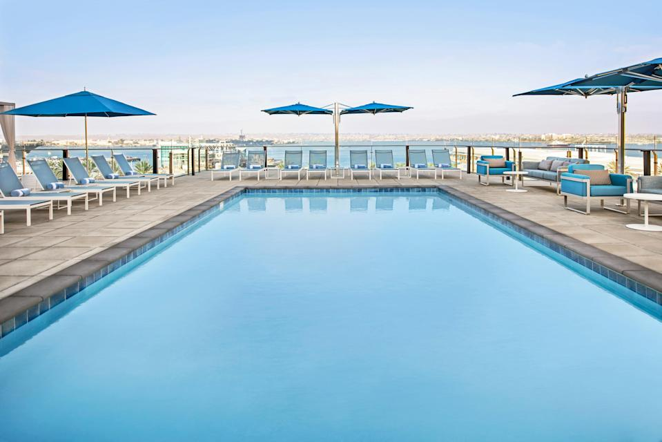 """<p><strong>Why did this hotel catch your attention?</strong><br> In a destination like San Diego, the view is everything. So it makes sense that the InterContinental capitalizes on its harbor location with floor-to-ceiling windows (in rooms and even in the fitness center) and a fourth floor pool overlooking the water. That means plenty of prime sunset vantage points, too. The vibe is classy-relaxed SoCal but don't expect much in the way of avant-garde design or decor.</p> <p><strong>What's the backstory?</strong><br> Hey there, sports fans! The hotel occupies part of historic Lane Field, the former home of the Pacific Coast League's San Diego Padres where Jackie Robinson once played (the MLB team now plays at nearby <a href=""""https://www.cntraveler.com/activities/san-diego/petco-park?mbid=synd_yahoo_rss"""" rel=""""nofollow noopener"""" target=""""_blank"""" data-ylk=""""slk:Petco Park"""" class=""""link rapid-noclick-resp"""">Petco Park</a>). Part of a $217 million bayfront project, the InterContinental shares the former ball field area with Marriott SpringHill Suites-Residence Inn.</p> <p><strong>Tell us all about the accommodations. Any tips on what to book?</strong><br> All 400 rooms have floor-to-ceiling windows, a nice touch considering the furnishings leave a little to be desired in terms of style or edge. Rooms come with robes and slippers, mini bars, marble bathrooms, and other standard amenities.</p> <p><strong>Is there a charge for Wi-Fi?</strong><br> The $30 daily amenity fee includes basic Wi-Fi, bottled water, a $25 food credit to the onsite Vistal restaurant, 20 percent off electric bike rentals, and a few other perks.</p> <p><strong>Drinking and dining—what are we looking at?</strong><br> The hotel's food-drink trifecta spans Vistal (Baja-inspired seafood with some meat dishes crafted by lauded local chef Amy DiBiase); Garibaldi (an outdoor """"speakeasy"""" with some Italian plates); and Layover (an aviation-themed rooftop lounge). From this hotel, you're also a quick ride to the re"""
