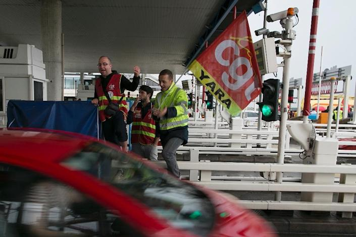 Members of the CGT trades union protest at a motorway toll booth at the Pont de Normandie between Le Havre and Honfleur on June 23, 2016 (AFP Photo/Charly Triballeau)