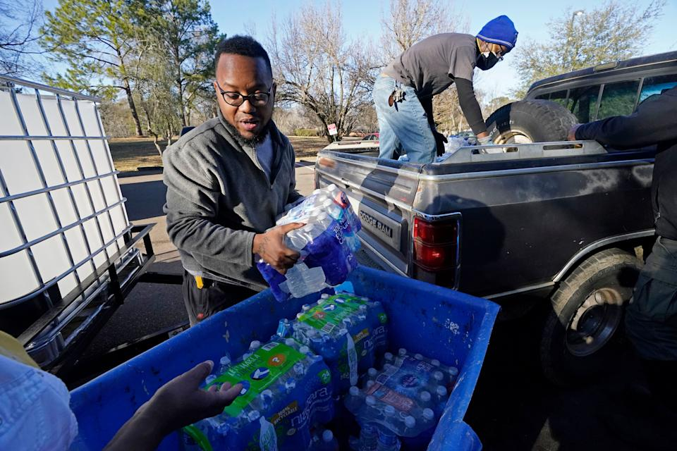 Lamar Jackson, left, stacks bottled water brought by Mac Epps of Mississippi Move at a senior residence in Jackson, Mississippi, on Feb. 22, 2021. Rising temperatures have melted the snow and ice in Mississippi, but tens of thousands of people still had little or no water service. (Photo: Rogelio V. Solis/AP)