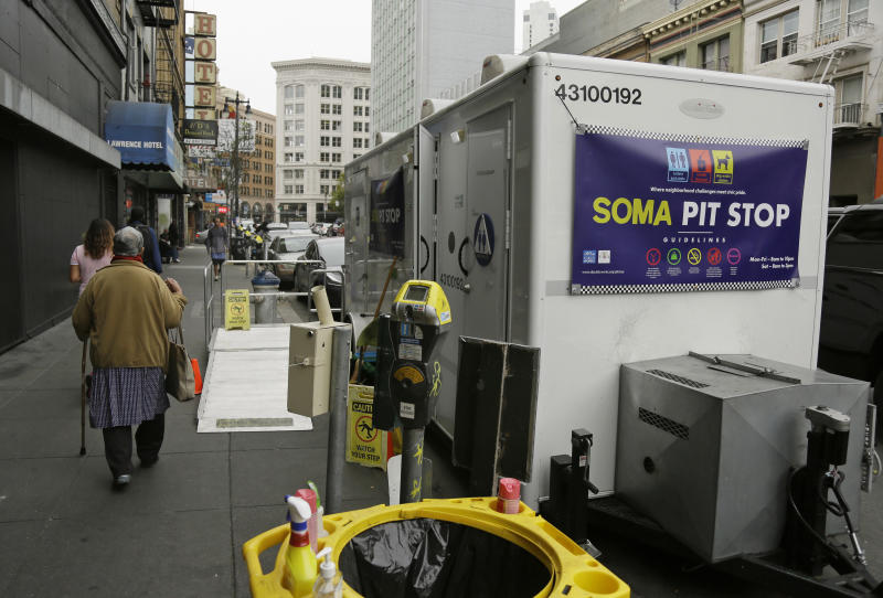 """A woman walks past a """"Pit Stop"""" public toilet on Sixth Street, Thursday, Aug. 1, 2019, in San Francisco. A 5-year-old portable toilet program in San Francisco that provides homeless people with a private place to go has expanded to 25 locations in the city and has spread to Los Angeles. Not everyone who uses the """"Pit Stop"""" toilets is homeless, but advocates say steam cleaning requests have dropped in surrounding areas. (AP Photo/Eric Risberg)"""
