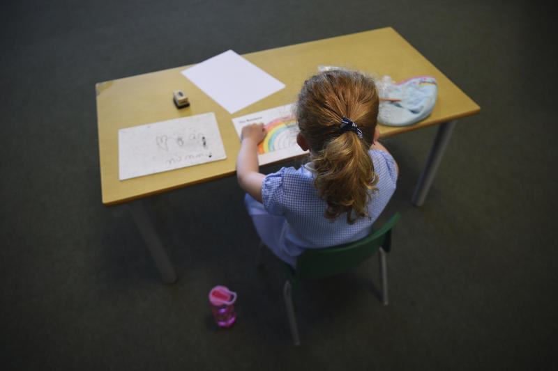 A pupil sits at a separate desk, as all students use social distancing at Hiltingbury Infant School in Chandler's Ford, England, as some pupils return to school as part of a wider easing of lockdown measures in England, Monday June 1, 2020. The British government has lifted some lockdown restrictions to restart social life, education, and activate the economy while still endeavouring to limit the spread of the highly contagious COVID-19 coronavirus. (Kirsty O'Connor/PA via AP)