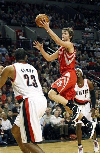 Houston Rockets' Chandler Parsons (25) laysup the ball as Portland Trail Blazers' Marcus Camby (23) and Gerald Wallace (3) defend in the first quarter during an NBA basketball game Wednesday, Feb. 8, 2012, in Portland, Ore. (AP Photo/Rick Bowmer)