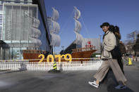 In this photo taken on Jan. 4, 2019, women pass by a new year decor outside a shopping mall in Beijing, China, China will slash taxes, step up spending and provide ample financing to private and small enterprises to help counter the country's worst slowdown since the global financial crisis amid a bruising trade war with the U.S., officials said Tuesday at a briefing on plans for 2019 that were set at an annual meeting in December. (AP Photo/Ng Han Guan)